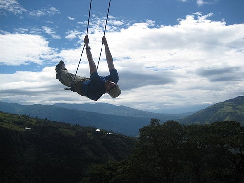 Swinging off the mountain near Baños, Ecuador