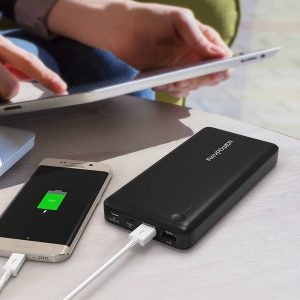 portable battery charger charging a phone and laptop