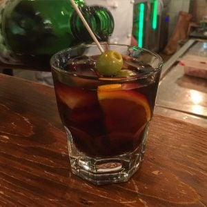 a glass of vermouth with olive