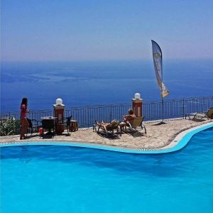 a pool overlooking a harbour in corfu greece