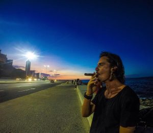a man smokes a cigar on el malecon havana cuba