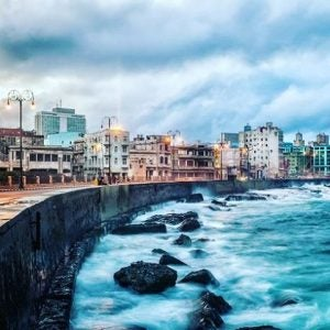 waves crash the boardwalk at el malecon havana