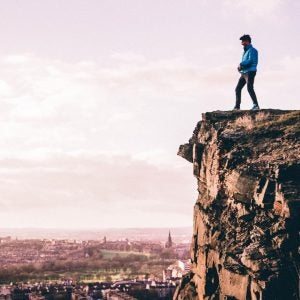 a man stands on a cliff overlooking edinburgh from arthur's seat