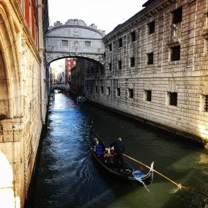 a gondolier steers his boat under the bridge of sighs in venice italy