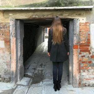 a woman tries to fit in a narrow street in venice italy