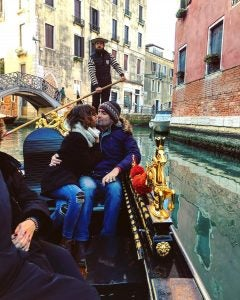 a couple kisses on a gondola ride in venice italy