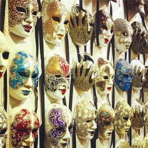 a wall of venetian masks on sale in venice italy