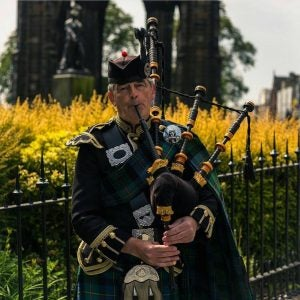 a man plays the bagpipes in front of the scott monument edinburgh