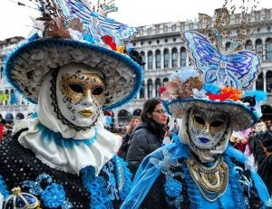 two people dressed in traditional masks at carnival venice