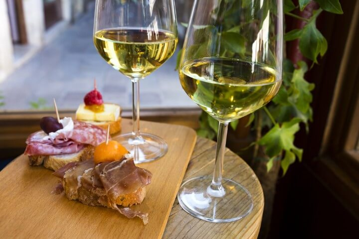 Cicchetti - italian tapas - with two wine glasses of white wine in venice - italy