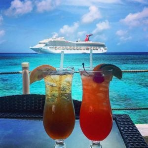 the view of a carnival cruiseship with two cocktail glasses