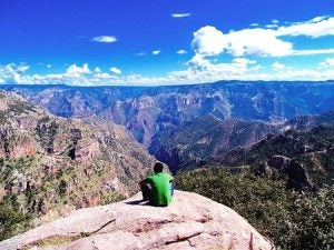 a hiker rests with a magnificent view over the copper canyon mexico