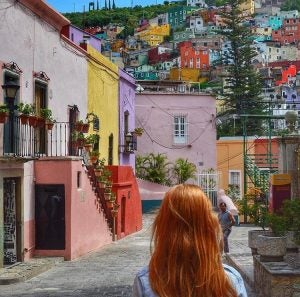 a woman looks up at the colourful buildings on a hill in guanajuato