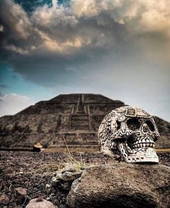 an ornate skull rests at the forefront of an ancient pyramid in teotihuacan mexico
