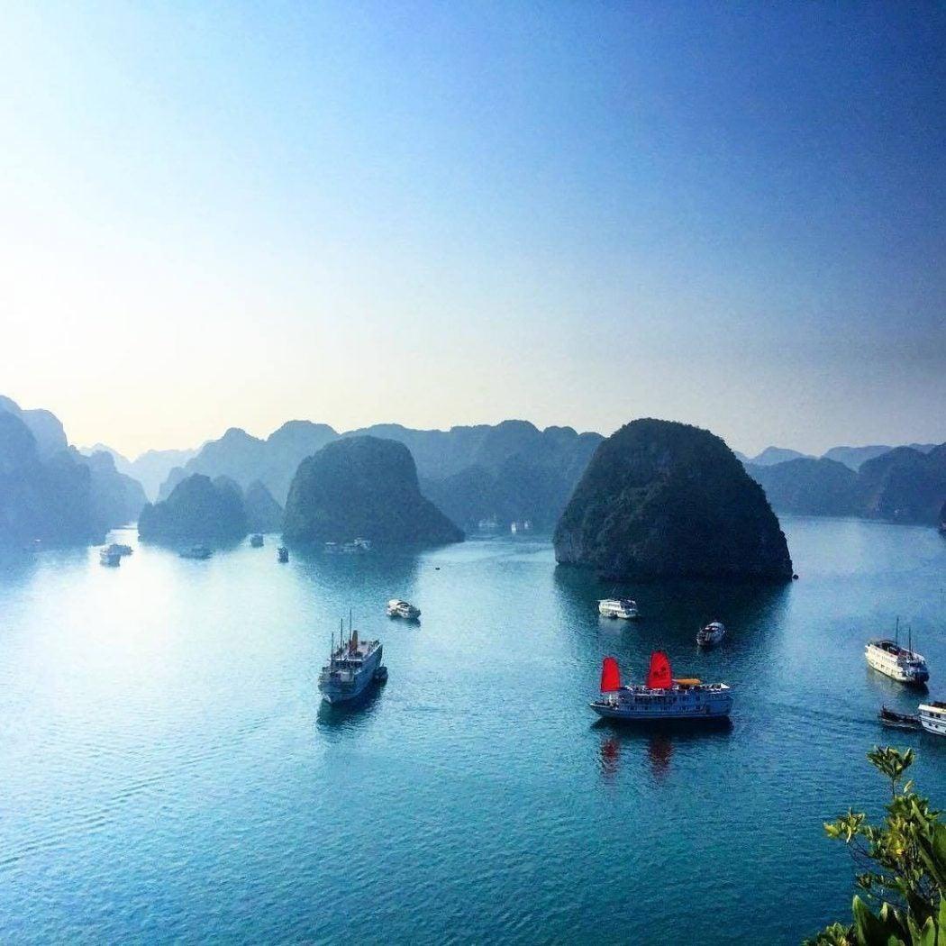 boats navigate through mountainous islands in vietnam
