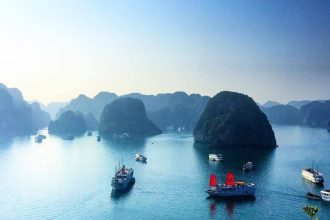 boats navigate through mountainous islands in vietnam