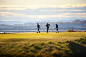 three players putting at st andrews golf course