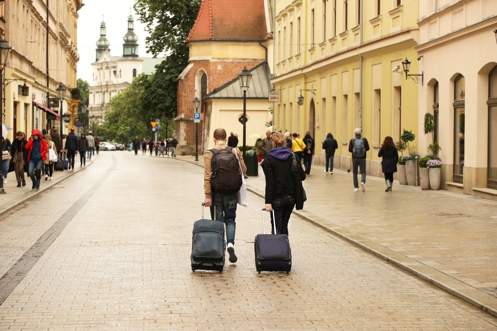 Two tourists walk carrying luggage in Krakow's city center, Poland
